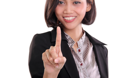 operating key: Close up portrait of an attractive Asian businesswoman pointing her index finger at the screen, isolated on white background Stock Photo