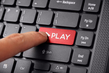 press button: Close up shot of a finger clicking the PLAY button on a laptop keyboard Stock Photo