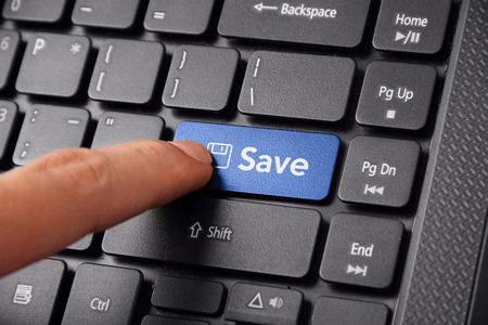 Close up shot of a finger clicking the SAVE button on a laptop keyboard