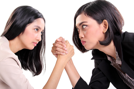 Side profile of two Asian business women doing arm wrestling and staring at each others eyes, closeup portrait isolated on white background