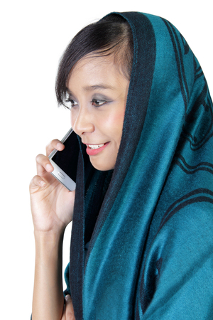 side profile: Side profile of an urban muslim woman making a phone call, isolated over white studio background Stock Photo