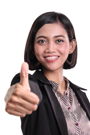 congratulating: Portrait of friendly Asian business woman congratulating with her thumb up, isolated on white background