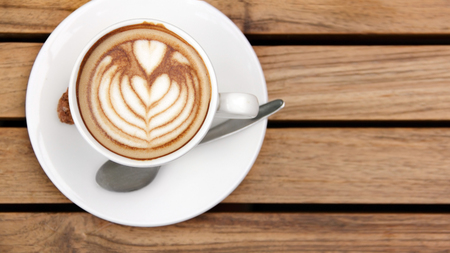 overhead shot: Overhead shot - a cup of cappuccino coffee laid on wooden table