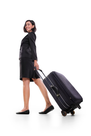 walking away: Businesswoman pulling a suitcase and walking away, full body shot isolated on white background Stock Photo