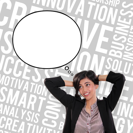 Attractive business woman looking up at empty thought bubble, over abstract typography art background of business concept