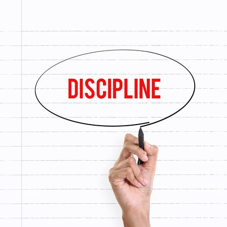 discipline: Hand drawing circle around the note DISCIPLINE, lined book page on the background