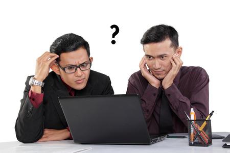 ホワイト バック グラウンドを分離、机の上のノート パソコンを見て 2 つのアジアのビジネスマンの困惑している表情 写真素材