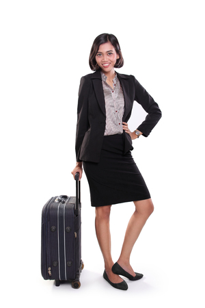 business traveller: Confident businesswoman posing with a travel bag, standing over white studio background Stock Photo