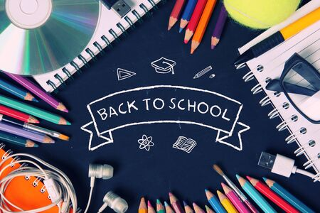 high angle view: Back to school wallpaper design. Hand drawn doodles framed with image of creative students supplies, filtered in retro color