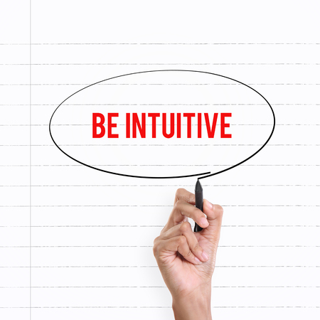 be aware: Hand drawing circle around the note BE INTUITIVE, lined book page on the background Stock Photo
