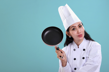 pan asian: An Asian female chef holding a cooking pan, copy space on light blue background