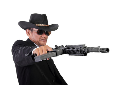 mobster: Angry mobster firing his gun maniacally, holding it horizontal with one hand, isolated on white background Stock Photo