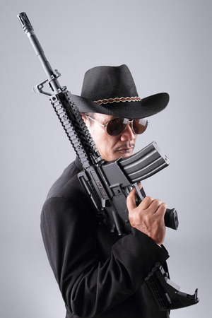 side profile: Side profile of a professional assassin dressed in stylish flamboyant cowboy fashion, posing with his black rifle