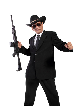mobster: Full length shot of a mobster in black fashionable outfits posing with his weapon, isolated on white background