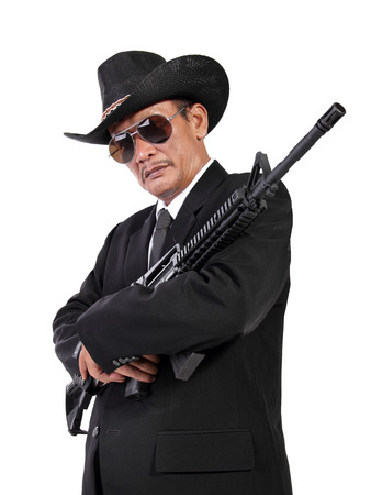 hitman: Portrait of an expert hitman dressed in classic western fashion, posing with a gun on his chest, isolated on white background Stock Photo