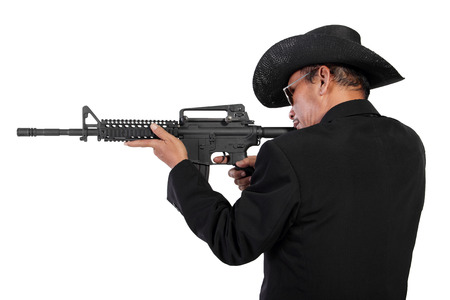 gangster background: Cowboy  gangster  hunter shooting with a rifle, picture taken from his back side, isolated over white background Stock Photo