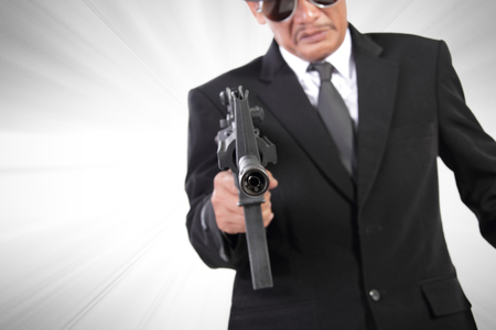 action movie: Pointed gun of a man in black suit, crime action movie concept background, with dramatized effect