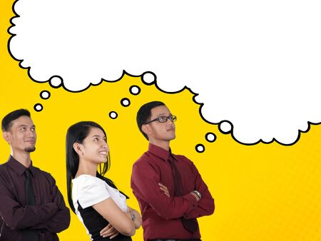 looking up: Dreams of success. Three business people looking up at empty white comic cloud  thought bubble for copyspace, over yellow background