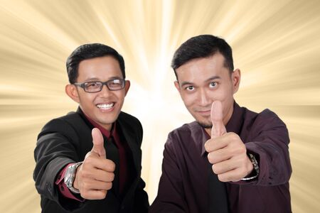 two thumbs up: Two businessmen showing thumbs up, over bright golden light background - bonus reward promotion concept