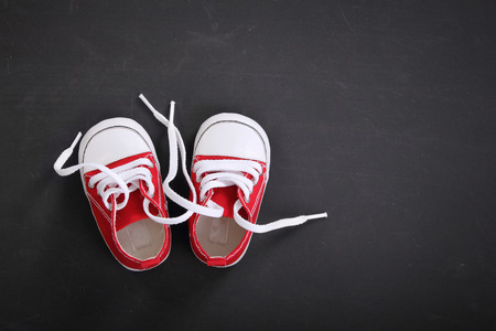 Cute tiny red baby sneakers overhead shot on blackboard for copy space Archivio Fotografico