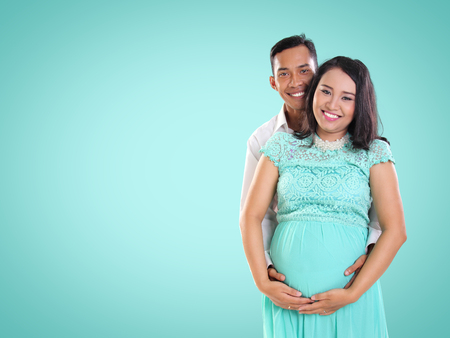 Fun cheerful smiling Asian couple during pregnancy standing over fresh mint colored background for copyspace
