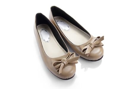 Flat shoes made of beige colored leather decorated with ribbon, displayed on isolated white space