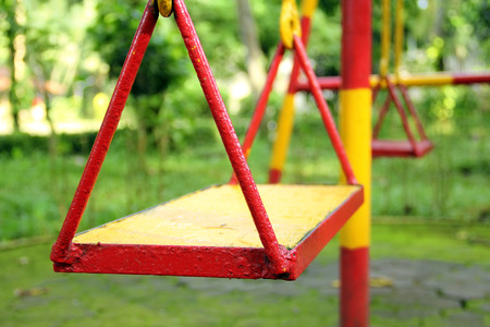 swing set: Swing set on a playground, painted in red and yellow colors Stock Photo