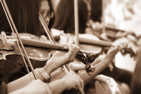 Unrecognized violinists playing their instruments, in sepia filtered portrait Stock Photo