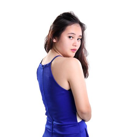 back shot: Back shot portrait of Asian girl in blue top, turning her face towards camera, isolated on white background