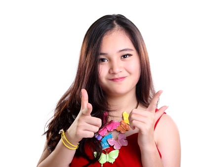 Close up portrait of attractive Asian girl pointing her index fingers at camera cheerfully, isolated over white background
