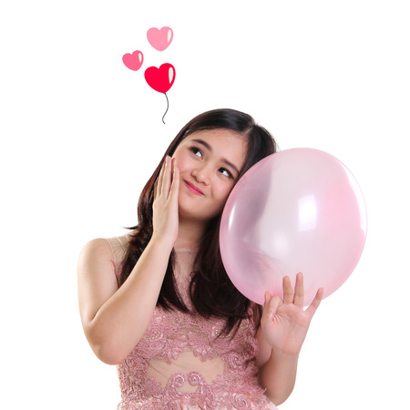 Sweet girl imagination of love, looking at heart shaped pictures above while holding a balloon Stock Photo
