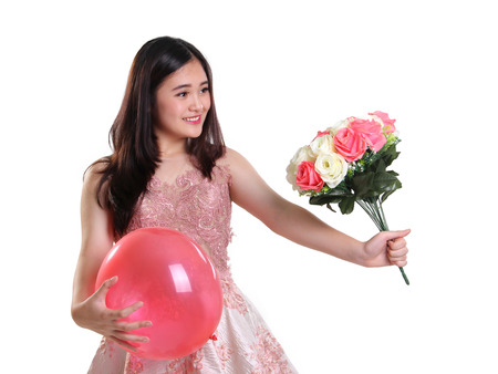 balloon bouquet: Nice young lady handing a bouquet of flower, while holding a pink balloon Stock Photo