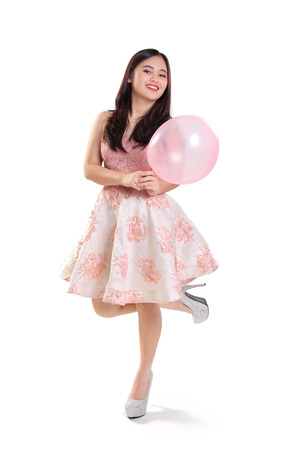 Pretty girl posing against white background while holding a balloon