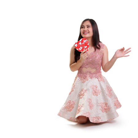arrodillarse: Lovely smiling Asian girl kneeling on the floor, holding a heart ornamented box, looking at copy space, isolated on white background