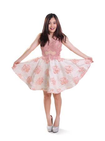 full shot: Cheerful girl posing in a dress, lifting her skirt playfully, full body shot isolated over white Stock Photo