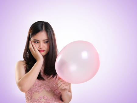 disappoint: Portrait of a sad girl looking at her balloon, against light purple background
