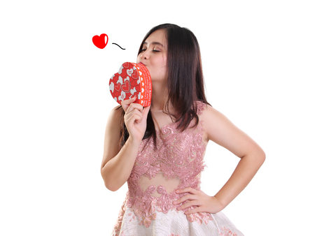 girl in love: Pretty girl kissing a heart shaped gift box, isolated over white background Stock Photo