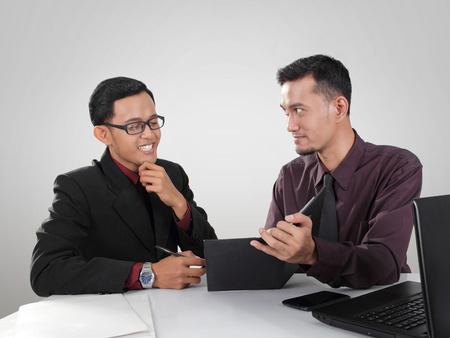 2 男性の企業の労働者は事務所の会合を持ちます。1 つ自信を持って実業家らしい興味がある彼の仕事仲間にノート パソコンでプレゼンテーションを