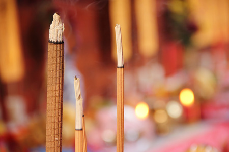 Closeup shot of burning incense sticks in a Chinese temple altar Stock Photo