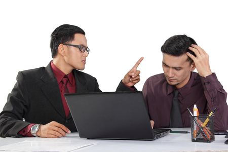 Two businessmen having an argument in their workplace. One angry businessmen with pointed finger blaming his partner upon a failure. Isolated on white