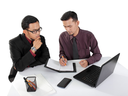 One male worker writing something on a note book page, while his associate paying attention. Both sitting on office table. Isolated over white background