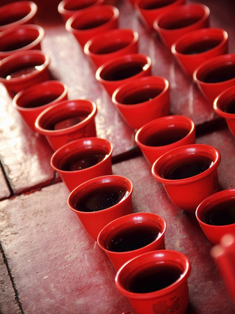 religious event: Rows of tea cups on an altar table for religious ceremonial event at a Chinese temple Stock Photo
