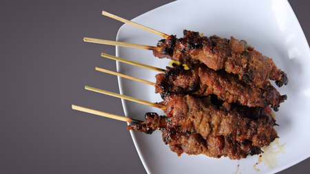 indonesian food: Top view of chicken satay (famous traditional Indonesian food) served in a plate with copyspace for design on grey background