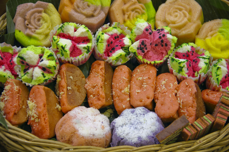 Various and colorful traditional Indonesian snacks in a rattan basket. Bolu kukus, pukis, etc. Stock Photo