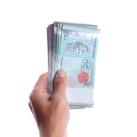 白で分離されたマレーシア ・ リンギットのお金の束を示す手