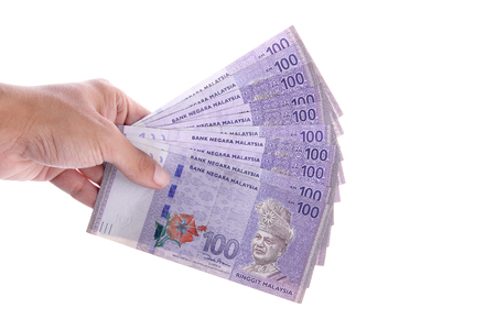 Hand holding some 100 Malaysian Ringgit money, isolated over white