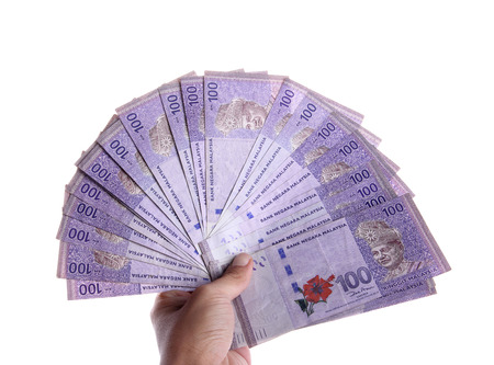 Malaysian Ringgit money in 100 nominal spreaded hand held, isolated over white background