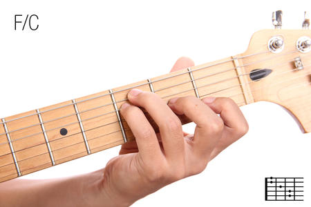FC - guitar keys tutorial series. Closeup of hand playing F on C chord, isolated on white background Stock Photo