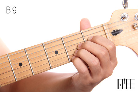 B9 - advanced guitar keys series. Closeup of hand playing B dominant ninth chord, isolated on white background
