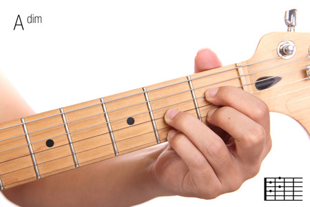Adim - advanced guitar keys series. Closeup of hand playing A diminished chord, isolated on white background Stock Photo